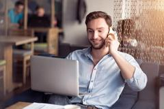 Delighted smiling guy talking on cell phone - stock photo