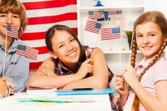 Smiling students with American flags at the class Stock Photos