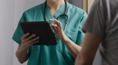 Doctor using a tablet,  consulting with senior patient - stock footage
