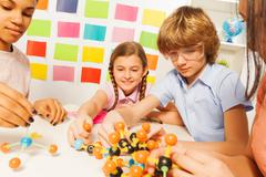 Young boy and girls assembling molecule model Stock Photos