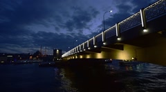 Istanbul, time lapse of sea traffic under illuminated low bridge, evening - stock footage