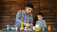 Father and son paint colors ceramic pottery Stock Footage
