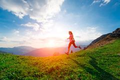 Female athlete trains running in the hillside meadows at sunset - stock photo