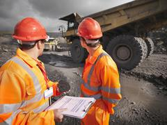 Workers Inspecting Trucks In Coal Mine - stock photo