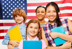 Smiling American teenage students with textbooks Stock Photos