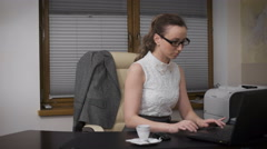 Young business woman has sat in the office till late. She drinks coffee and - stock footage