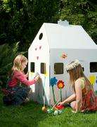 Girls painting a cardboard wendy house Kuvituskuvat