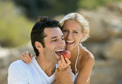 A female feeding a latin man a nectarine Stock Photos