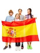Four multiethnic teenage kids holding Spanish flag Stock Photos