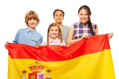 Happy multiethnic teenage kids with flag of Spain Stock Photos