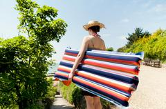 A girl with a Lilo going to the beach - stock photo