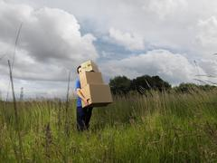 man carrying boxes through field - stock photo