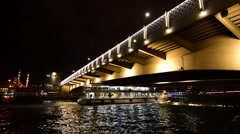 Istanbul, white passenger boat crossing the illuminated Galata Bridge, night Stock Footage