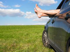 mans feet out of car window - stock photo