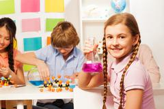 Schoolgirl with plaits holding flask at school lab Stock Photos