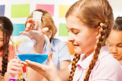 Schoolgirl holding flask with blue reagent at lab Stock Photos