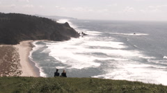 Pacific Coast Couple Sitting On Hillside Stock Footage