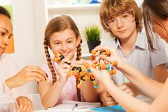 Kids assembling atomic chain with molecular model Kuvituskuvat