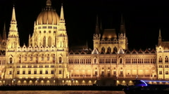 Parliament in Budapest at night while sailing on a boat on the river Danube.  Stock Footage