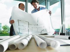 Architects looking at blue prints Stock Photos