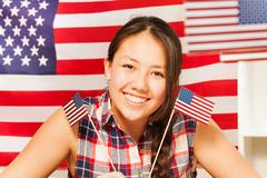 Smiling teenage Asian girl with flags of USA Stock Photos