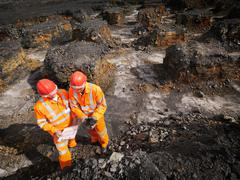 Workers Inspecting Coal In Mine - stock photo