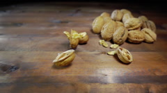 Walnuts falling on wooden table slow motion Stock Footage