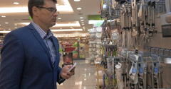 Man talking on phone and choosing utensil in the store Stock Footage
