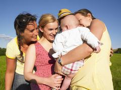 women admiring baby - stock photo