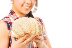 Smiling girl holding cerebrum model in her hands Kuvituskuvat