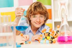 Boy in safety goggles holding flask at the lab Stock Photos