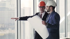 Architects talking with building plan in hands Stock Footage