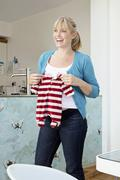 A young pregnant mum holding a baby grow Stock Photos