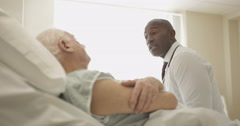 4K Friendly doctor comforting elderly patient at his bedside - stock footage