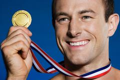 Male athlete holding a medal Stock Photos
