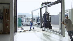 Workers in a window factory preparing a shipment to leave. - stock footage