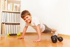 Kid boy working out on the floor, doing push-ups Stock Photos