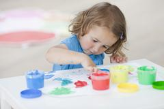 Young girl playing with colours Stock Photos