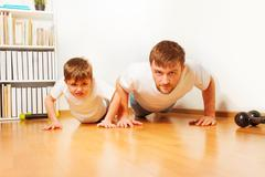 Father and son working up, doing pushups at home - stock photo
