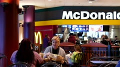 People eating foods and chatting at mcdonalds fast food restaurant - stock footage