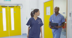 4K Cheerful colleagues in modern hospital chatting as they walk through building Stock Footage