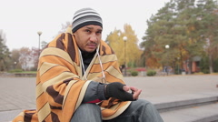 Helpless man sitting alone in city street, asking for help, woman giving charity Stock Footage