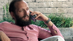 Young man talking on cellphone while sitting on sofa on patio - stock footage