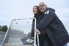 Middle aged couple on motor boat Kuvituskuvat