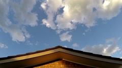Clouds pass over a rooftop of a suburban home. Time Lapse zoom in. - stock footage