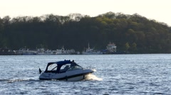 Motorboat runabout sailing in water lake sea river, jungle trees in background Stock Footage
