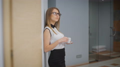 Young girl in the corridor with coffee in hand. Business woman lost in thought Stock Footage
