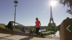 Female jogger running from camera into shot, with Eiffel tower in the Stock Footage