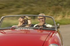Mid aged couple in sports car Stock Photos