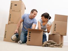 Couple unpacking kitchenware from boxes Stock Photos
